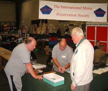 Photograph of Leicester 2009 FISTS stand showing Paul M0BMN, John M0CDL and Keith G3KYF discussing a tiny Australian straight key