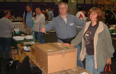 Photograph of Leicester 2009 FISTS stand showing Tony G3ZRJ, his XYL Sally and a large transceiver-size cardboard box.  In the background is John M0CDL and possibly Rob M0BPT